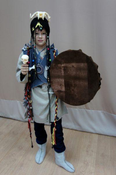 Правильно одетый и оснащенный мальчик - ученик шамана: юбочка, кофточка, головной убор с костями. Бубен и колотушка